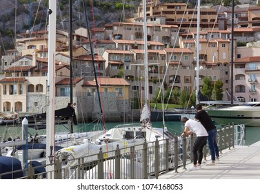 DUINO AURISINA, Italy - April 14, 2018: Two boys leant against a railing at the marina in Portopicclo, near Trieste, Italy