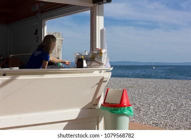 DUINO AURISINA, Italy - April 14, 2018: Blonde woman working at a beach bar in Sistiana seaside resort near Trieste