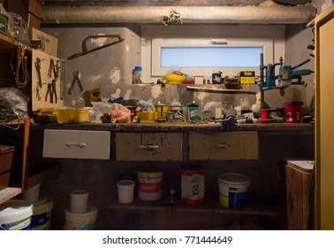 DUINO AURISINA, Italy - December 6, 2017: Very old dirty and messy garage workbench full of rusty tools, cans and boxes