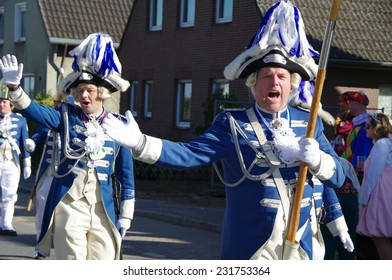 DUISBURG, GERMANY - 6 March 2011 An unidentified woman and man in the annual carnival costumes & masks are on the road. They give sweets to children and adults, play a musical instrument, having fun.