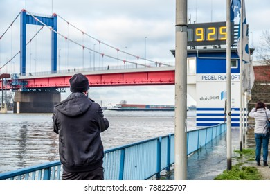 DUISBURG / GERMANY - JANUARY 08 2017 : Tourist observing the the river Rhine flooding the promenade in Ruhrort