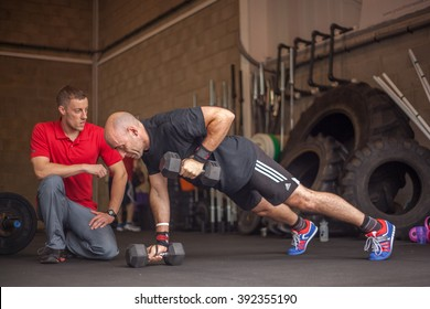 Dukinfield, Tameside, England - July 20, 2014: A man in a red shirt is kneeling while overseeing another man exercising with dumbbells in a push-up position. The exerciser has one dumbbell raised.