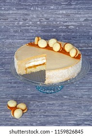 Dulce de leche alfajores round cake on stand, caramel mousse layered tort, vertical rustic photo on wooden background, cutted cake with cream filling, brown beige and blue picture