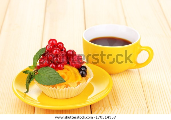 Dulcet cake with fruit and berries on wooden table
