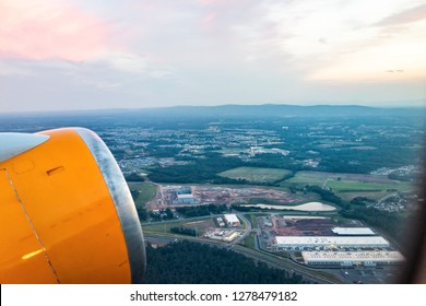 Dulles, USA International Airport, IAD, cityscape of Sterling with colorful sunset in Virginia evening night, buildings illuminated, airplane yellow engine