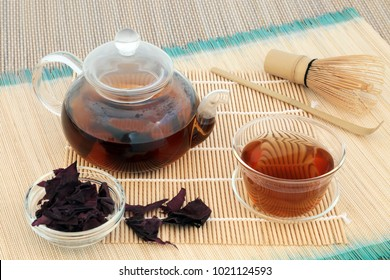 Dulse seaweed tea with glass teapot, tea cup and dried leaves with whisk and stirrer on bamboo background. Health drink very high in minerals.