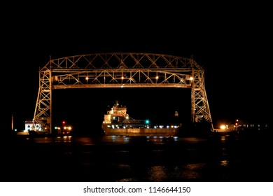 Duluth Minnesota aerial lift bridge with ore ship in canal entering harbor at night