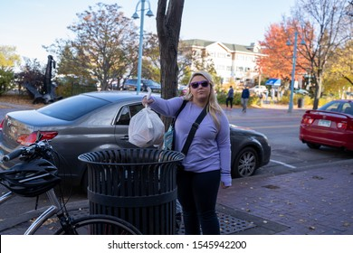 Duluth, Minnesota - October 20, 2019: Adult woman throws a bag of trash into a trash can in Canal Park. Concept for not littering