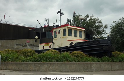 Duluth, MN/US - Sept 1, 2019:  Historic Bayfield tugboat in front of Army Corp of Engineers building.  Canal Park, cloudy sky
