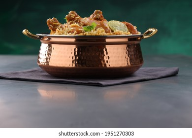 Dum chicken biriyani, close up image of Kerala-Thalassery biriyani  which is mixed with masalaarranged in a copper serving bowl and garnished with lemon slices  placed on graphite textured. - Shutterstock ID 1951270303