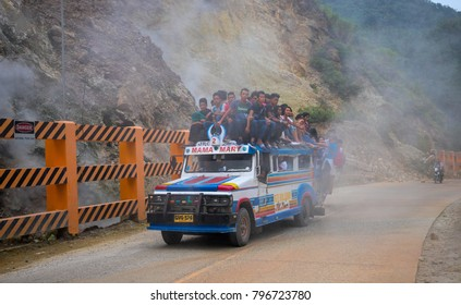 Dumaguete, Philippines - 18 January, 2018: Philippines public transport jeepney with people on roof in mountain fog clouds. Public transport in volcano mountains. Philippines jeepney car on road