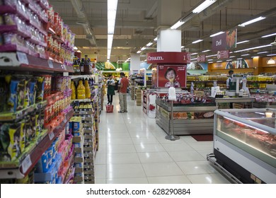 Dumaguete, Philippines - 26 November, 2016: Food supermarket in shopping mall. Asian supermarket. Shopping mall banner template. Sweets and desserts on shop display. Buyer and seller in shop interior