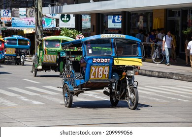 DUMAGUETE, PHILIPPINES - FEBRUARY 18, 2014 :Tricycle motor taxi, Philippines inexpensive transport service. Tricycle motor taxi are the most popular means of public transportation in the Philippines.