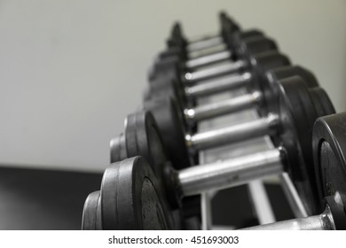 Dumb bells lined up in a fitness studio. picture is short focus.