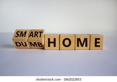 Dumb or smart home . Hand turns cubes and changes the words 'dumb home' to 'smart home'. Beautiful yellow table, white background. Business and smart home concept. Copy space.