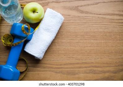 dumbbell and apple on desk