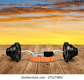 Dumbbell with belt and gloves on wooden floor at sunset