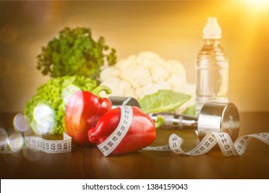 Dumbbell with bottled water , measuring tape and vegetables isolated on white background