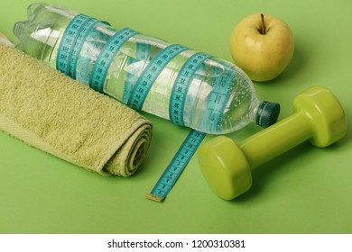 Dumbbell in bright green color, water bottle, measure tape, towel and fruit on green background. Sports regime equipment. Barbell made of plastic by juicy green apple. Diet and sport regime concept