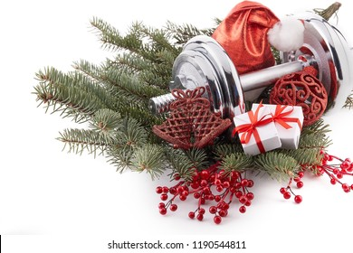 Dumbbell, fir tree branches, gifts and Christmas decorations isolated on a white background. New Year and Christmas. Fitness. Healthy lifestyle.