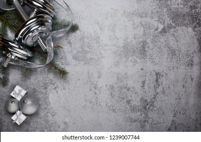 Dumbbell, fir tree branches, gifts and Christmas decorations  on a gray background. New Year and Christmas. Fitness. Healthy lifestyle.