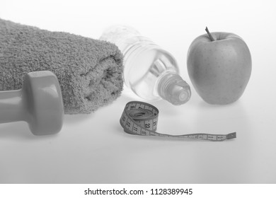 Dumbbell in green color, water bottle, measure tape, towel and fruit on grey background. Sports and healthy regime equipment. Diet and sport regime concept. Barbell made of plastic near green apple.