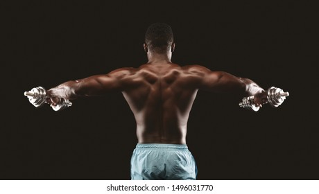 Dumbbell Lateral Raise. African bodybuilder lifting hands with dumbbells up, black studio background, back view