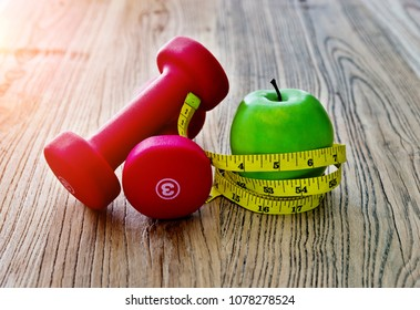 Dumbbell measuring tape and green apple on table