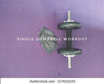 A dumbbell and pair of glove on the exercise mat. Fitness concept of single dumbbell workout and high intensity training (HIIT).