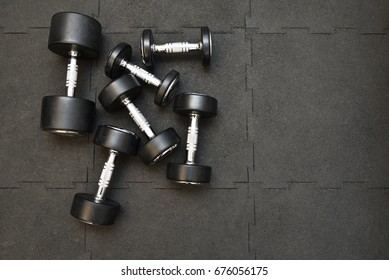 Dumbbell placed on black rubber tile floor in fitness room.