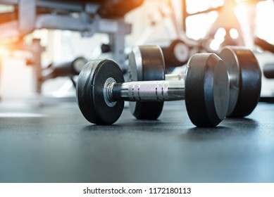 The dumbbell put on ground floor,at fitness gym,blurry light around