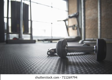 Dumbbell and Rope on the floor in the Gym with treadmill in background