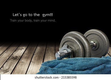 a dumbbell and a towel is on the wooden floor