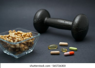 Dumbbell, walnuts and dietary supplements on dark background: fitness and muscle building concept.