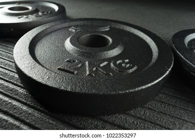 Dumbbell weight plates on a fitness studio gym floor