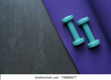 dumbbell and yoga mat on table, fitness healthy and sport concept