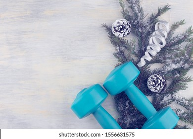 Dumbbells against the background of a spruce branch with Christmas decorations. The concept of sports lifestyle, weight loss, exercise, energy charge, emotion charger. Top view, flat lay. Copy space.