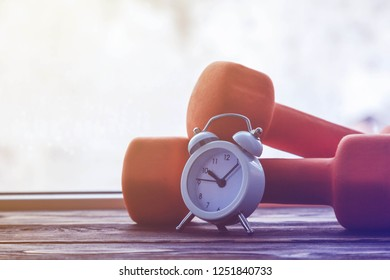 dumbbells and alarm clock on the window in winter, copy space, concept of morning exercises