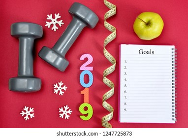 Dumbbells with apple and open notebook on red background. Healthy resolutions for the New Year 2019.