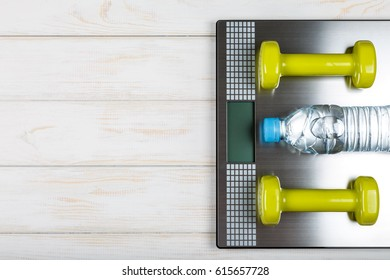 Dumbbells and bottle of water lying on the scales on white wood background. Concept plan.