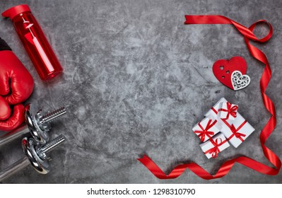 Dumbbells, boxing gloves, bottle for water, gift boxes and red hearts on grey background.Top view with copy space. Valentine's Day card. Fitness, sport and healthy lifestyle concept.