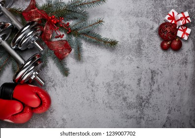 Dumbbells, boxing gloves,  fir tree branches and Christmas decorations on a gray background.Top view with copy space. New Year and Christmas. Fitness, sport and healthy lifestyle concept.