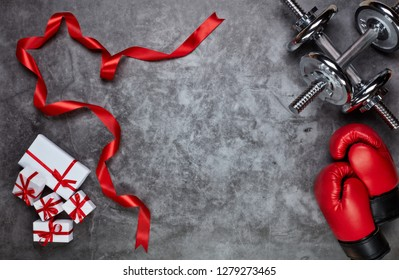 Dumbbells, boxing gloves, gift boxes on grey background.Top view with copy space. Valentine's Day card. Fitness, sport and healthy lifestyle concept.