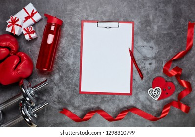 Dumbbells, boxing gloves, gift boxes, red hearts, bottle for water and tablet with blank sheet on grey background.Top view. Valentine's Day card. Fitness, sport and healthy lifestyle concept.