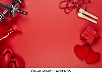 Dumbbells, boxing gloves, rope, bottle for water, gift box and two red hearts on a red background.Top view with copy space. Valentine's Day card. Fitness, sport and healthy lifestyle concept.
