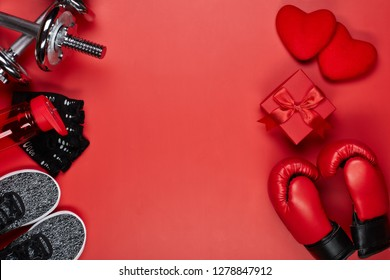 Dumbbells, boxing gloves, rope, bottle for water, gift box and two hearts on a red background.Top view with copy space. Valentine's Day card. Fitness, sport and healthy lifestyle concept.