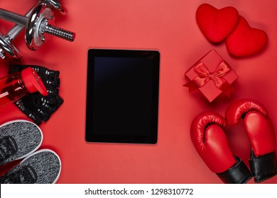 Dumbbells, boxing gloves, rope, bottle for water, computer tablet, gift box and two hearts on red background.Top view with copy space. Valentine's Day card. Fitness, sport, healthy lifestyle concept.