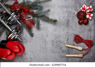 Dumbbells, boxing gloves, rope,  fir tree branches and Christmas decorations on a gray background.Top view with copy space. New Year and Christmas. Fitness, sport and healthy lifestyle concept.