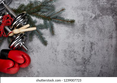 Dumbbells, boxing gloves, rope,  fir tree branches on a gray background.Top view with copy space. New Year and Christmas. Fitness, sport and healthy lifestyle concept.