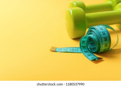 Dumbbells in bright green color isolated on yellow background. Barbells made of plastic near long soft ruler. Shaping and sport regime concept. Sports equipment and cyan measuring tape in roll